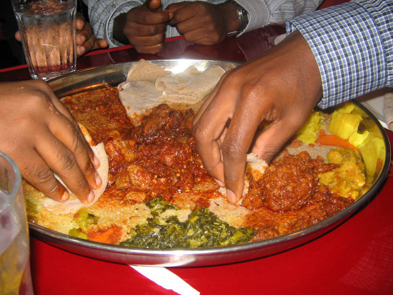 Diners eating from a platter of Ethiopian dishes