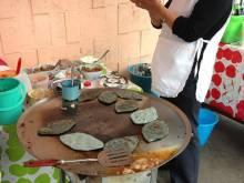 Woman making blue corn tlacoyos