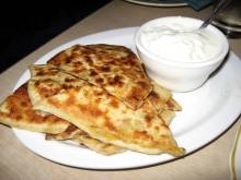 A plate of bolani with a side of yogurt