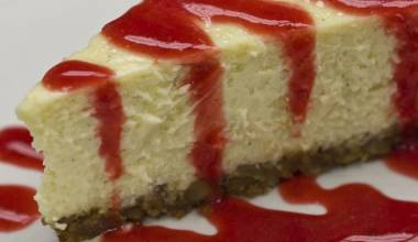 A slice of cheesecake with raspberry sauce