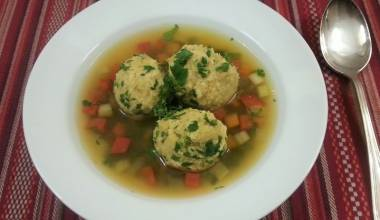 A bowl of chicken broth with gundi dumplings